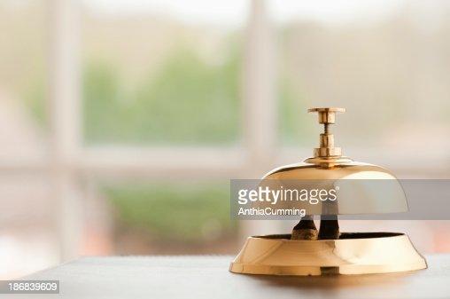 Brass service bell sitting on a reception desk beside window