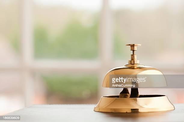 Cloche de service en laiton assis sur une réception au bord de la fenêtre