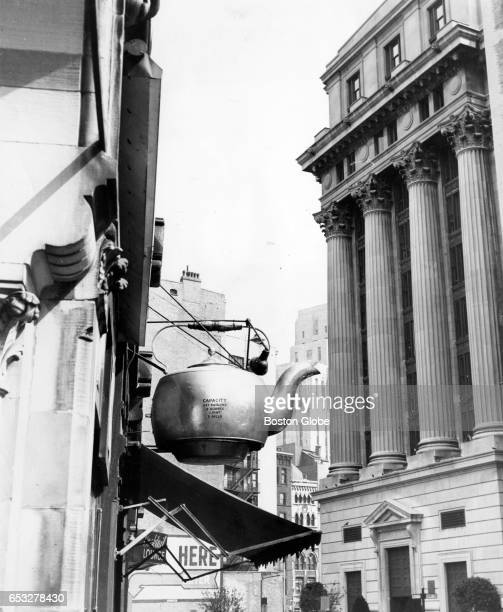A brass teapot forms a unique signpost for Oriental Tea Co on Court Street in Boston Aug 9 1961 The steaming kettle as well as City Hall Annex in...