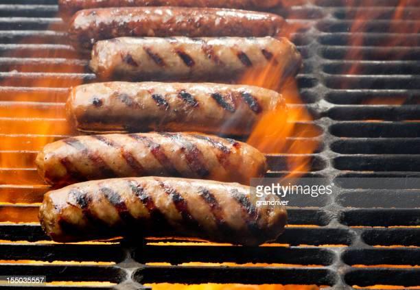 Bratwurst und Hot Dogs auf dem Grill mit Flammen