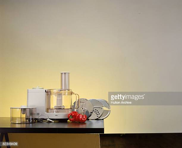 A Braun food processor is shown with all its assorted blades and attachments alongside two red peppers 1970s