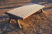 Braune mit Raureif überzogene Sitzbank aus Holz