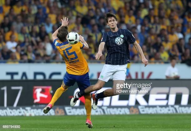 Braunschweig's Swedish forward Christoffer Nyman and Wolfsburg's defender Philipp Wollscheid vie for the ball during German Bundesliga relegation...
