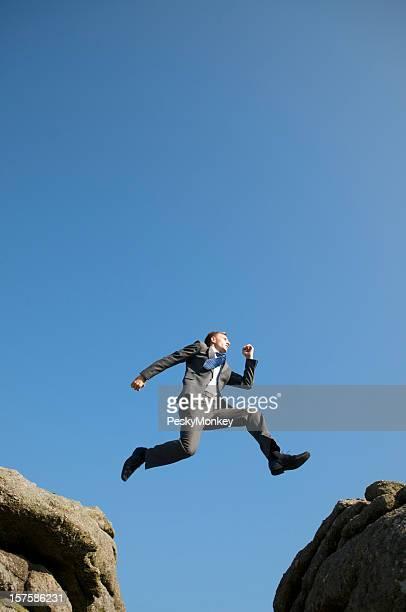Brave Geschäftsmann springen zwischen Felsen Blue Sky