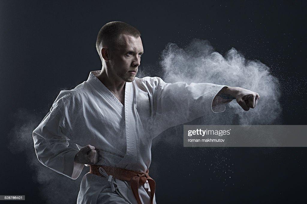Brave fighter in kimono doing karate