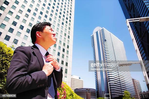 Brave Japanese businessman adjusts necktie before going to work