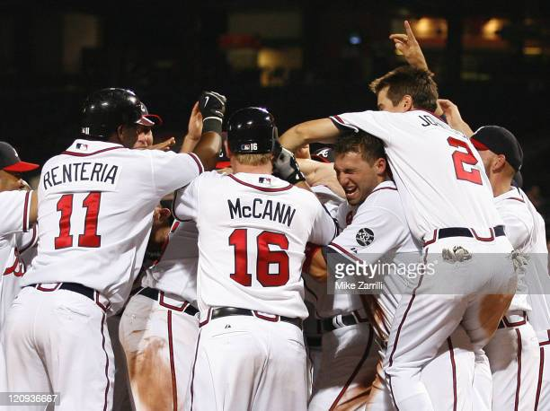 Braves players Edgar Renteria Brian McCann Jeff Francoeur and Kelly Johnson pounce on Andruw Jones after his game winning home run during the game...