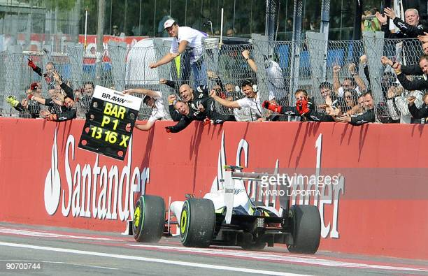 Brawn GP's mechanics celebrate as Brazilian driver Rubens Barrichello passes by the pit wall of the Autodromo Nazionale circuit on September 13 2009...