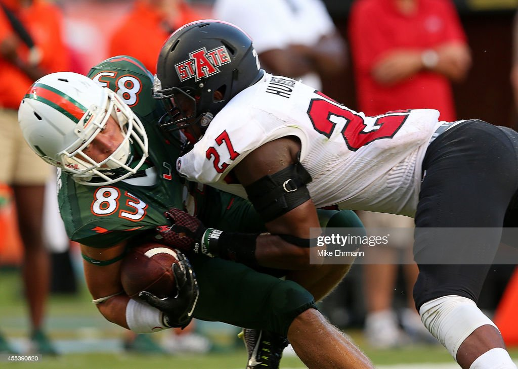 Braxton Berrios of the Miami Hurricanes is tackled after a catch by Money Hunter of the Arkansas State Red Wolves during a game at Sunlife Stadium on...