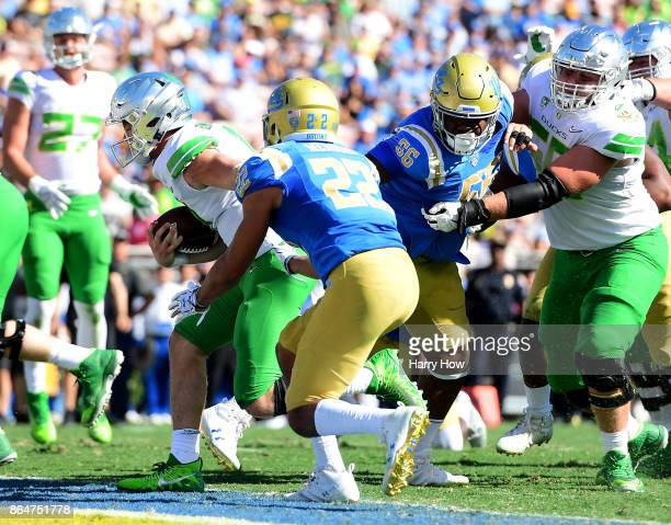 Braxton Burmeister of the Oregon Ducks scores a running touchdown in front of Nate Meadors of the UCLA Bruins to tie the game 1414 during the first...