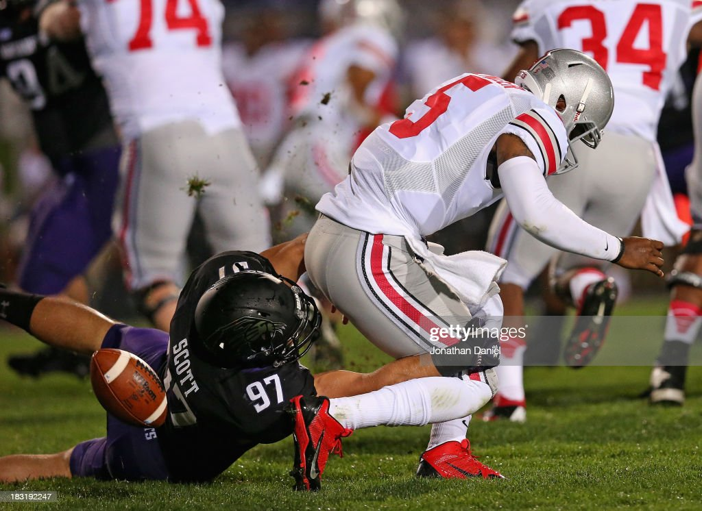 <a gi-track='captionPersonalityLinkClicked' href=/galleries/search?phrase=Braxton+Miller&family=editorial&specificpeople=7122480 ng-click='$event.stopPropagation()'>Braxton Miller</a> #5 of the Ohio State Buckeyes fumbles the ball as he is tackled by Tyler Scott #97 of the Northwestern Wildcats at Ryan Field on October 5, 2013 in Evanston, Illinois.
