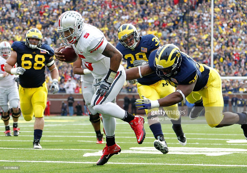 <a gi-track='captionPersonalityLinkClicked' href=/galleries/search?phrase=Braxton+Miller&family=editorial&specificpeople=7122480 ng-click='$event.stopPropagation()'>Braxton Miller</a> #5 of the Ohio State Buckeyes gets in for a second quarter touchdown past Kenny Demens #25 of the Michigan Wolverines at Michigan Stadium on November 26, 2011 in Ann Arbor, Michigan.