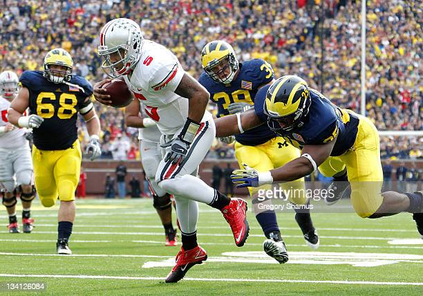 Braxton Miller of the Ohio State Buckeyes gets in for a second quarter touchdown past Kenny Demens of the Michigan Wolverines at Michigan Stadium on...