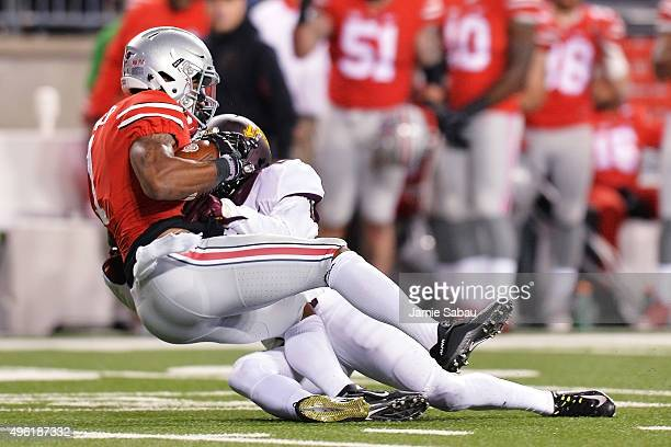 Braxton Miller of the Ohio State Buckeyes is brought down by Briean BoddyCalhoun of the Minnesota Golden Gophers in the fourth quarter after catching...