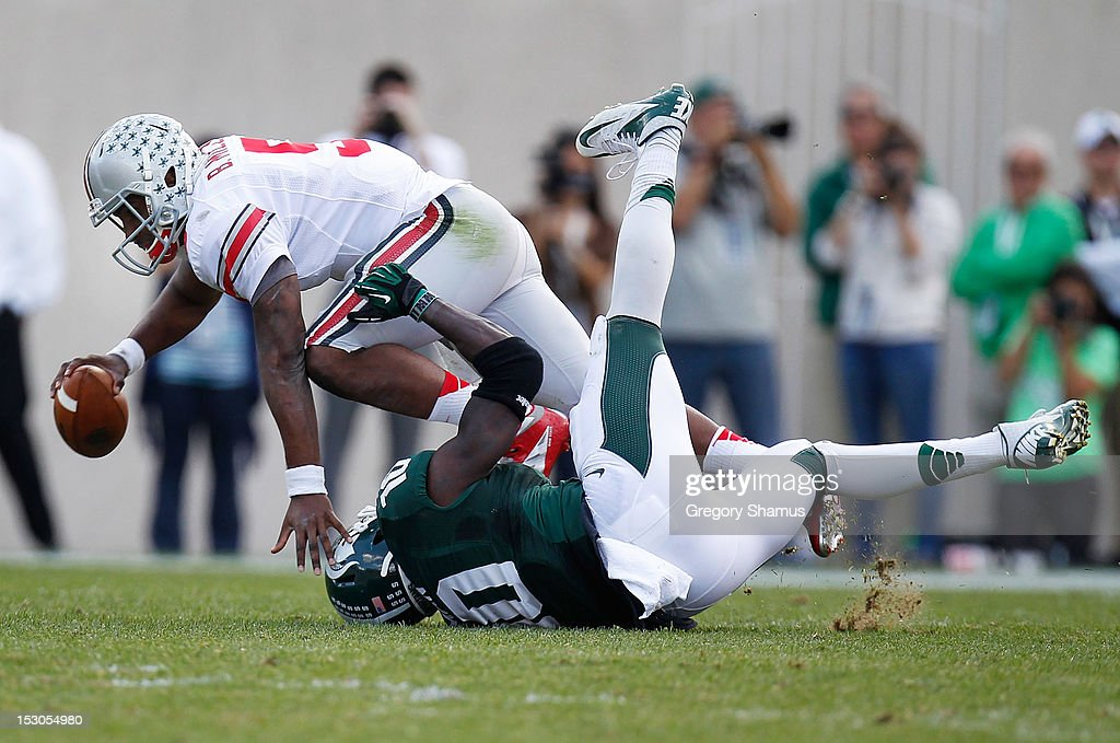 <a gi-track='captionPersonalityLinkClicked' href=/galleries/search?phrase=Braxton+Miller&family=editorial&specificpeople=7122480 ng-click='$event.stopPropagation()'>Braxton Miller</a> #5 of the Ohio State Buckeyes is sacked in the second quarter by Chris Norman #10 of the Michigan State Spartans at Spartan Stadium on September 29, 2012 in East Lansing, Michigan.