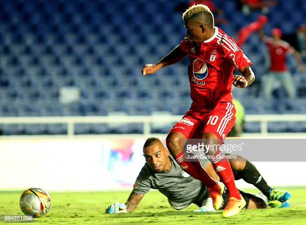 Brayan Angulo of America de Cali dribbles past Carlos Chavez goalkeeper of Atletico FC to score the third goal of his team during a match between...