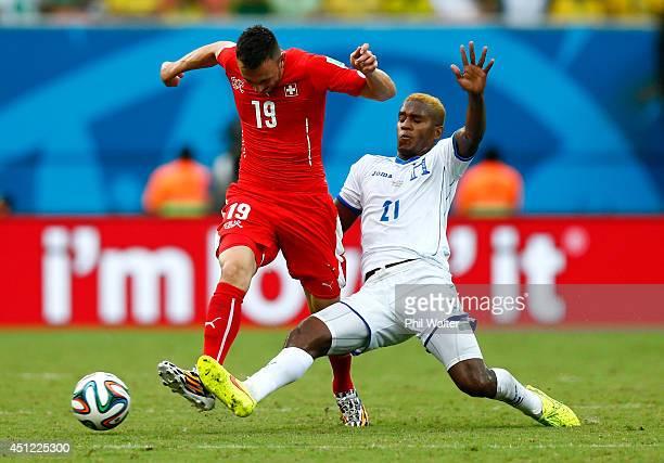 Brayan Beckeles of Honduras challenges Josip Drmic of Switzerland during the 2014 FIFA World Cup Brazil Group E match between Honduras and...
