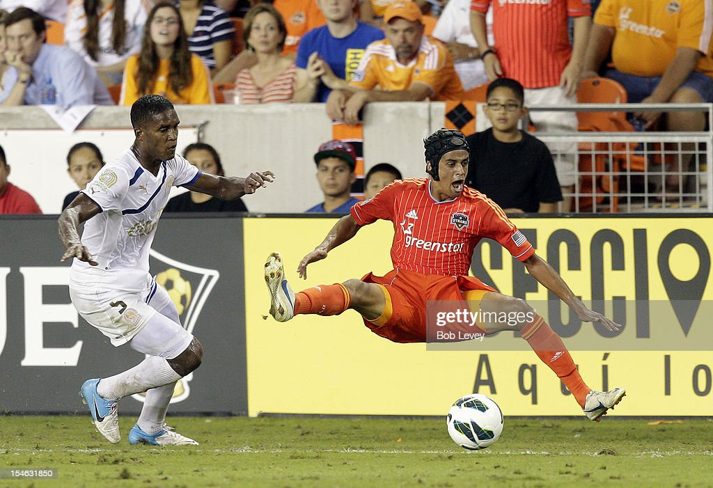 Brayan Beckles of the Olimpia gives Calen Carr of the Houston Dynamo a shove out of bounds as Carr had beaten him down the sideline in the second...