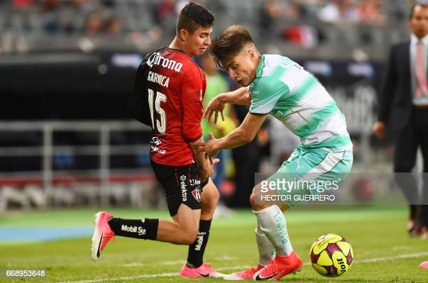 Brayan Garnica of Atlas vies for the ball with Jorge Flores of Santos during their Mexican Clausura 2017 tournament football match at Jalisco stadium...