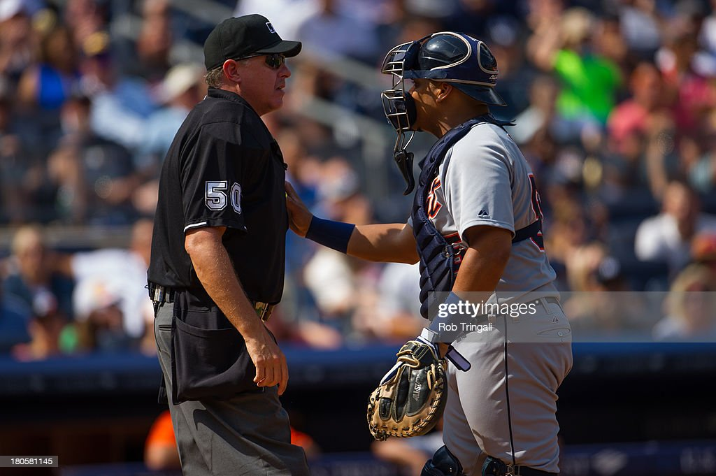 Brayan Pena #55 of the Detroit Tigers holds back the home plate umpire after an argument over a call made during the game at Yankee Stadium on August 11, 2013 in the Bronx borough of Manhattan.