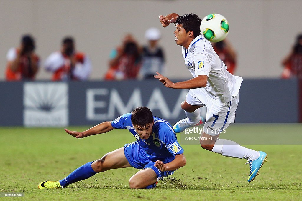 Brayan Velasquez (R) of Honduras is challenged by Akramjon Komilov of Uzbekistan during the FIFA U-17 World Cup UAE 2013 Round of 16 match between Honduras and Uzbekistan at Sharjah Stadium on October 28, 2013 in Sharjah, United Arab Emirates.