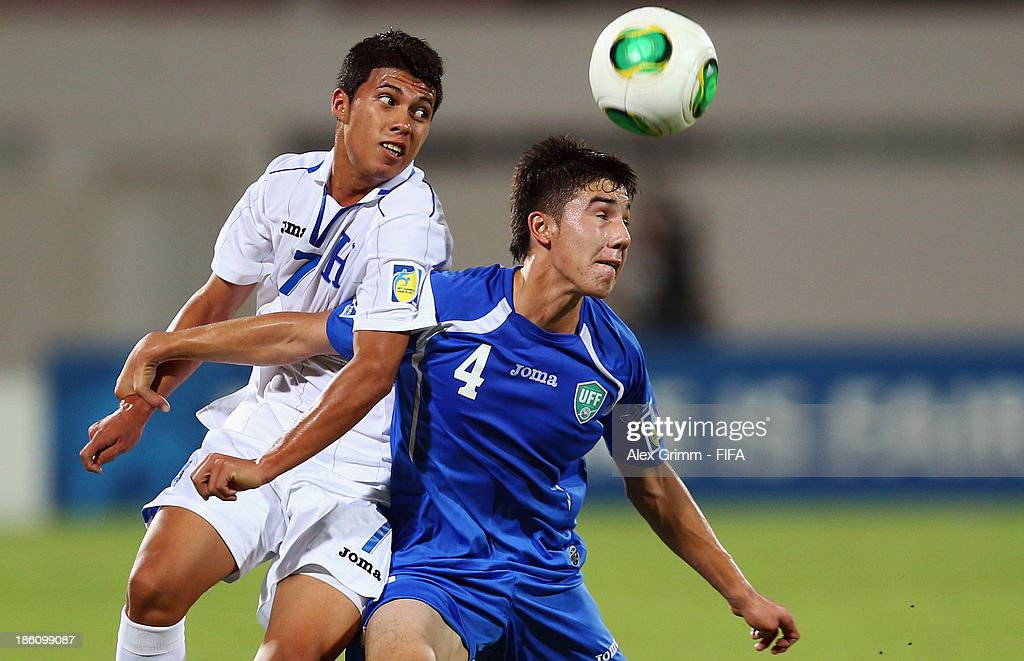 Brayan Velasquez (L) of Honduras is challenged by Akramjon Komilov of Uzbekistan during the FIFA U-17 World Cup UAE 2013 Round of 16 match between Honduras and Uzbekistan at Sharjah Stadium on October 28, 2013 in Sharjah, United Arab Emirates.