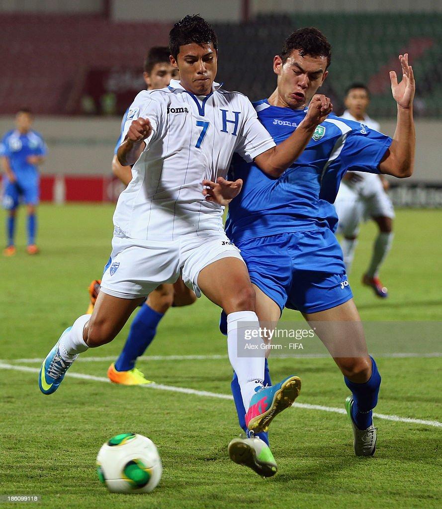 Brayan Velasquez (L) of Honduras is challenged by Rustamjon Ashurmatov of Uzbekistan during the FIFA U-17 World Cup UAE 2013 Round of 16 match between Honduras and Uzbekistan at Sharjah Stadium on October 28, 2013 in Sharjah, United Arab Emirates.