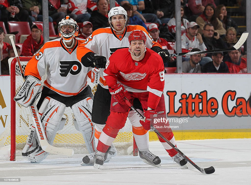 Brayden Coburn #5 of the Philadelphia Flyers gives <a gi-track='captionPersonalityLinkClicked' href=/galleries/search?phrase=Tomas+Holmstrom&family=editorial&specificpeople=203288 ng-click='$event.stopPropagation()'>Tomas Holmstrom</a> #96 of the Detroit Red Wings a shot in the back in a game on January 2, 2011 at the Joe Louis Arena in Detroit, Michigan. The Flyers defeated the Wings 3-2.