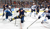 Brayden McNabb of the Buffalo Sabres stick handles the puck from his knees as Andrew Ladd of the Winnipeg Jets defends while Tyler Myers of the...