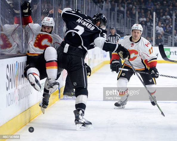 Brayden McNabb of the Los Angeles Kings checks Brandon Bollig of the Calgary Flames in front of Lance Bouma during the first period at Staples Center...