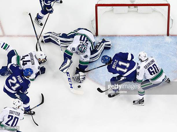 Brayden Point and Brian Boyle of the Tampa Bay Lightning look for the puck against goalie Ryan Miller Erik Gudbranson and Markus Granlund of the...