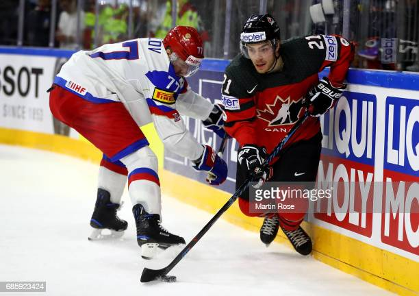 Brayden Point of Canada challenges Anton Belov of Russia for the puck during the 2017 IIHF Ice Hockey World Championship semi final game between...