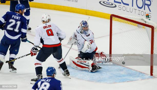 Brayden Point of the Tampa Bay Lightning shoots the puck for a goal against Dmitry Orlov and Philipp Grubauer of the Washington Capitals during the...