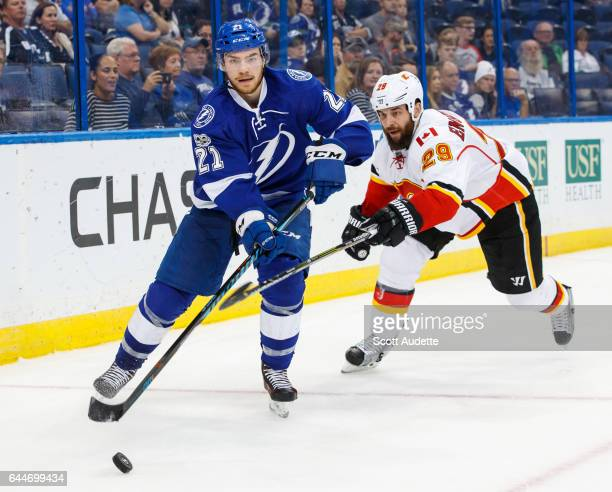 Brayden Point of the Tampa Bay Lightning skates against Deryk Engelland of the Calgary Flames during the third period at Amalie Arena on February 23...