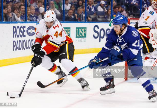 Brayden Point of the Tampa Bay Lightning skates against Matt Bartkowski of the Calgary Flames during the third period at Amalie Arena on February 23...