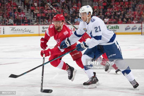 Brayden Point of the Tampa Bay Lightning skates up ice next to Luke Glendening of the Detroit Red Wings during an NHL game at Little Caesars Arena on...