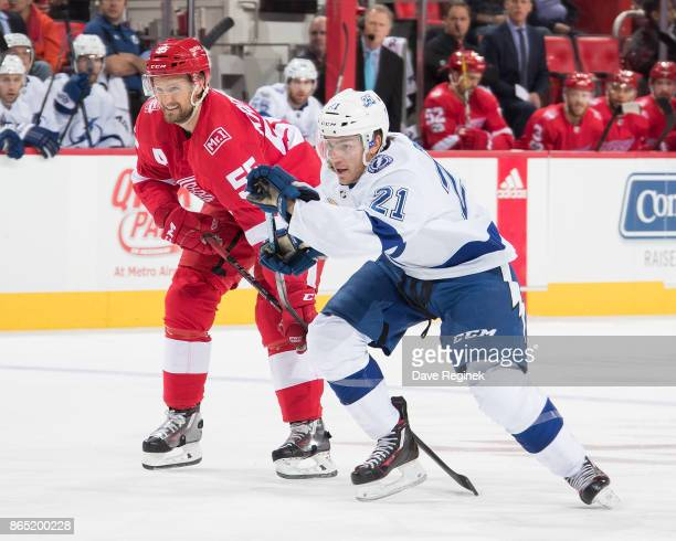 Brayden Point of the Tampa Bay Lightning skates up ice next to Niklas Kronwall of the Detroit Red Wings during an NHL game at Little Caesars Arena on...