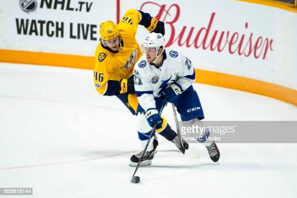 Brayden Point of the Tampa Bay Lightning skates with the puck as Pontus Aberg of the Nashville Predators chases during a NHL preseason game at...