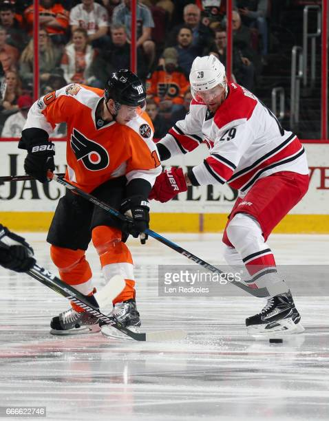 Brayden Schenn of the Philadelphia Flyers battles for the loose puck with Bryan Bickell of the Carolina Hurricanes on April 9 2017 at the Wells Fargo...