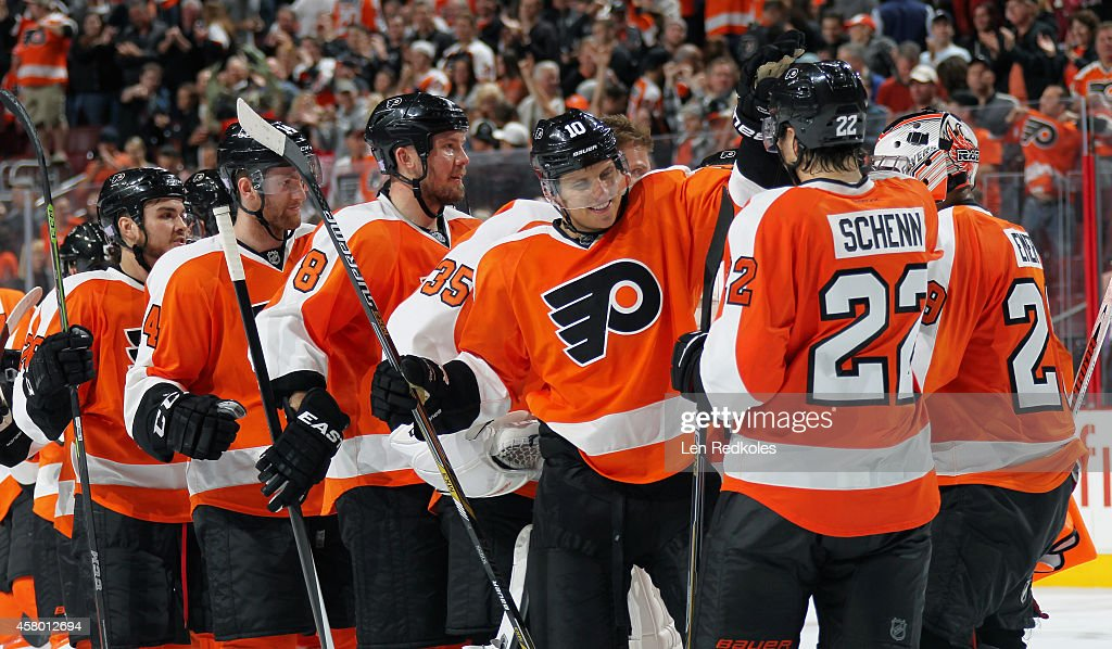 Brayden Schenn #10 of the Philadelphia Flyers celebrates his game-winning overtime goal against the Los Angeles Kings with his brother Luke Schenn #22 and their teammates on October 28, 2014 at the Wells Fargo Center in Philadelphia, Pennsylvania.