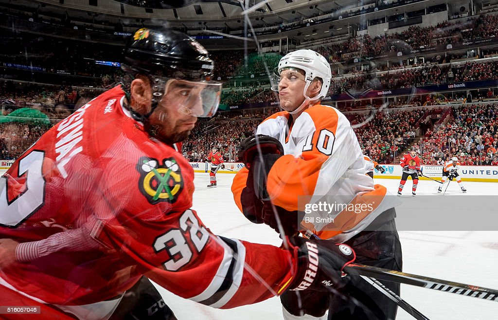 Brayden Schenn #10 of the Philadelphia Flyers gets ready to hit Michal Rozsival #32 of the Chicago Blackhawks into the boards in the third period of the NHL game at the United Center on March 16, 2016 in Chicago, Illinois.