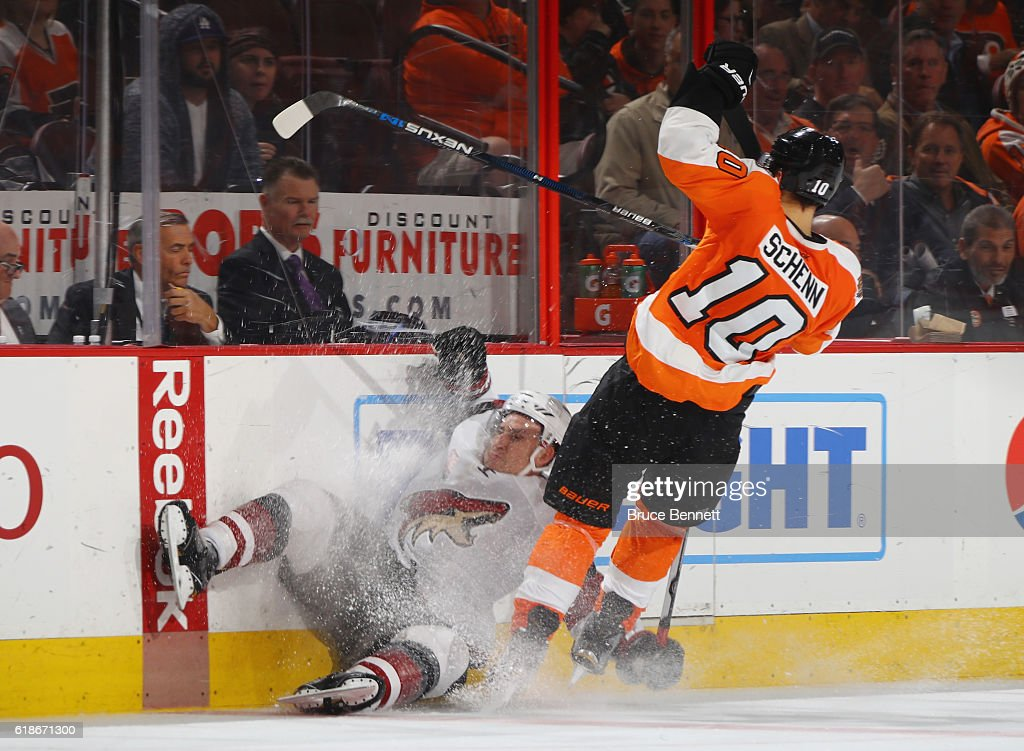 Brayden Schenn #10 of the Philadelphia Flyers hits Michael Stone #26 of the Arizona Coyotes into the boards during the third period at the Wells Fargo Center on October 27, 2016 in Philadelphia, Pennsylvania. The Coyotes defeated the Flyers 5-4.