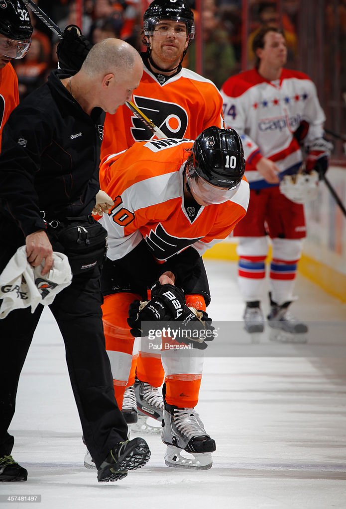 Brayden Schenn #10 of the Philadelphia Flyers is helped off the ice by Trainer Jim McCrossin after being injured during the second period of an NHL hockey game against the Washington Capitals at Wells Fargo Center on December 17, 2013 in Philadelphia, Pennsylvania.