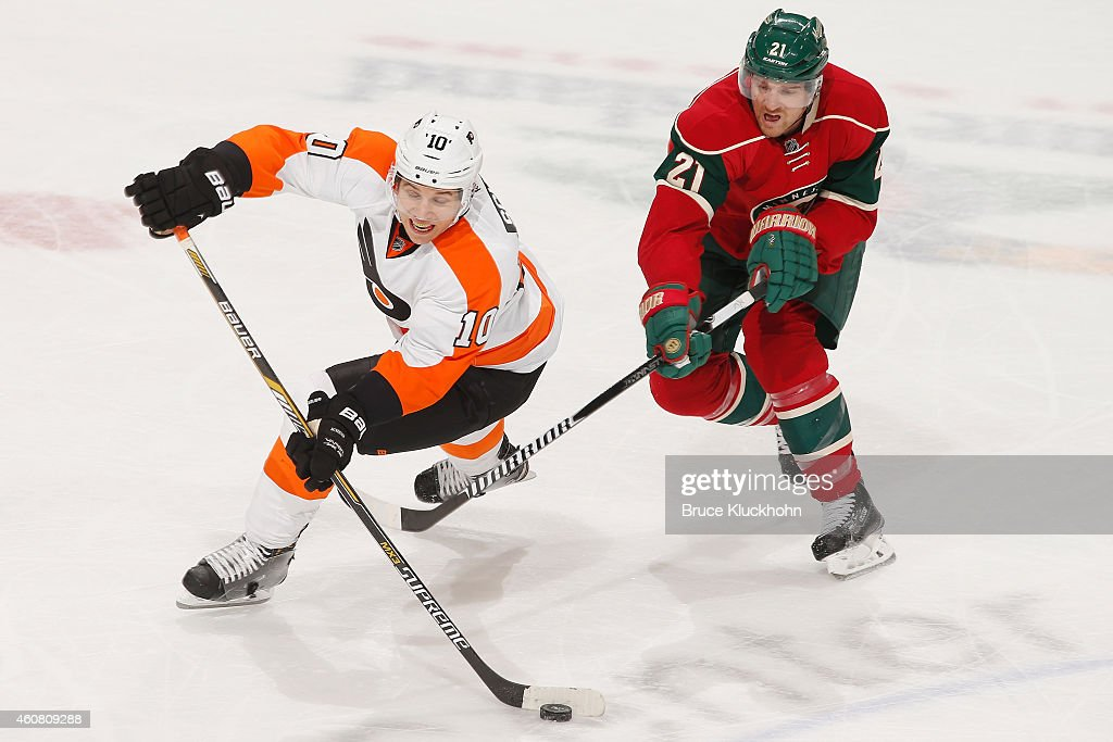Brayden Schenn of the Philadelphia Flyers passes the puck with Kyle Brodziak of the Minnesota Wild defending during the game on December 23 2014 at...