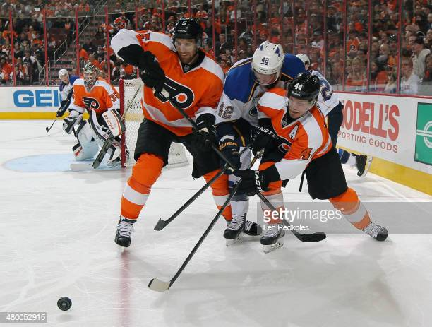 Braydon Coburn and Kimmo Timonen of the Philadelphia Flyers battle for the loose puck in the corner with David Backes of the St Louis Blues on March...