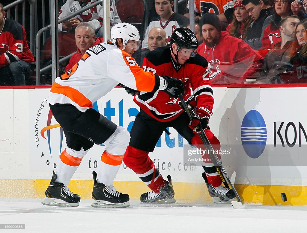 Braydon Coburn #5 of the Philadelphia Flyers and Ryan Carter #20 of the New Jersey Devils battle for a loose puck during the Devils' home opener at the Prudential Center on January 22, 2013 in Newark, New Jersey.