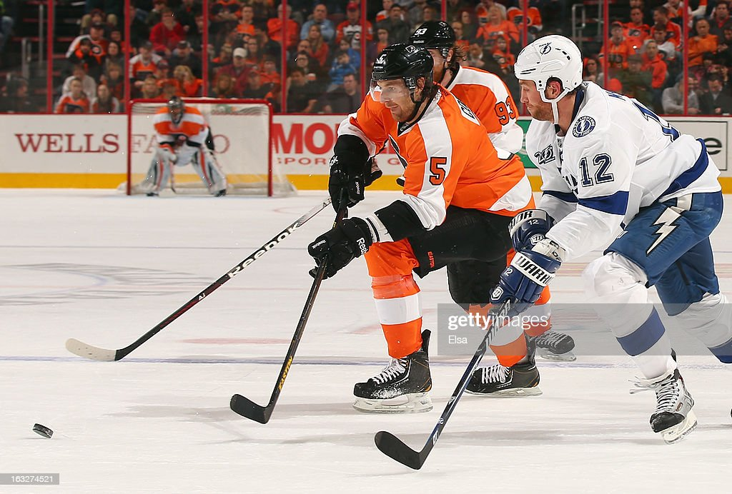 Braydon Coburn #5 of the Philadelphia Flyers and Ryan Malone #12 of the Tampa Bay Lightning chase after the puck on February 5, 2013 at the Wells Fargo Center in Philadelphia, Pennsylvania.