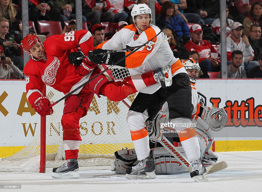 Braydon Coburn #5 of the Philadelphia Flyers knockes <a gi-track='captionPersonalityLinkClicked' href=/galleries/search?phrase=Tomas+Holmstrom&family=editorial&specificpeople=203288 ng-click='$event.stopPropagation()'>Tomas Holmstrom</a> #96 of the Detroit Red Wings out of the way in a game on January 2, 2011 at the Joe Louis Arena in Detroit, Michigan. The Flyers defeated the Wings 3-2.