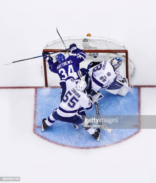 Braydon Coburn of the Tampa Bay Lightning pushes Auston Matthews of the Toronto Maple Leafs into the net in front of Andrei Vasilevskiy of the Tampa...