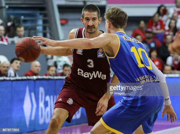 Braydon Hobbs of Bayern Muenchen and Thomas Klepeisz of Braunschweig battle for the ball during the easyCredit BBL Basketball Bundesliga match...